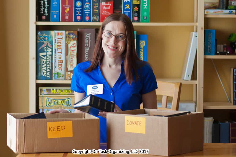 Photo of professional organizer, Nancy Haworth, with 2 boxes, one labeled keep and the other labeled donate