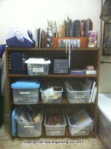 Craft room organization photo of a bookcase with containers of card making supplies
