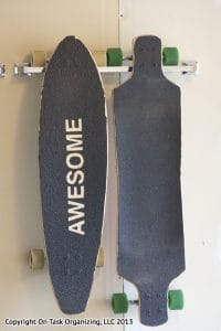 Two longboards stored by hanging on a towel rack on a garage