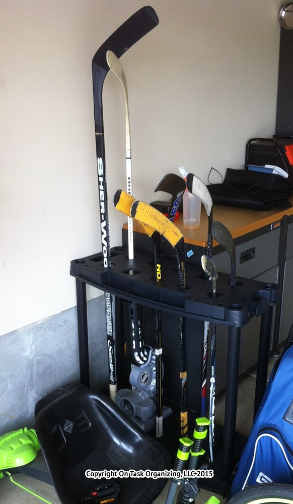 This rake holder was repurposed to hold hockey sticks in a garage during a garage organizing session with On Task Organizing, LLC in Raleigh, NC