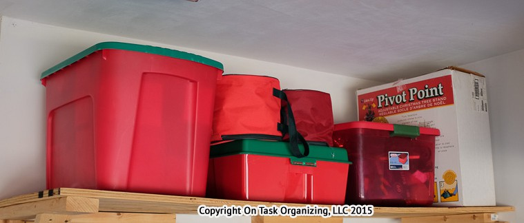 Organizing Holiday Decorations in red bins on a shelf